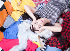 A woman lying on a pile of her clothes, not able to choose her favourite